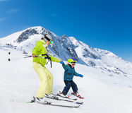 Instructor and kid skiing down the mountain Stock Photos