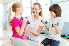 Instructor with kids. Cheerful instructor helping children with exercising in health club stock photography
