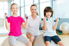 Instructor with kids. Cheerful instructor helping children with exercising in health club royalty free stock photography