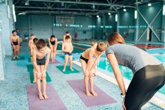 Instructor kids doing exercises before swimming. Woman instructor and group of kids doing exercises before swimming. Healthy and happy childhood concept Royalty Free Stock Photography