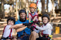 Instructor and kids forming hand stack in park. Smiling instructor and kids forming hand stack in park Royalty Free Stock Image