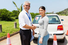 Instructor learner driver handshaking. Senior driving instructor and learner driver handshaking in testing ground Royalty Free Stock Photography