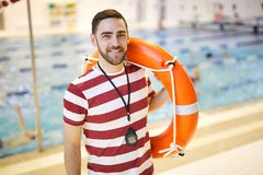 Instructor with lifebuoy. Portrait of smiling swim instructor standing and holding lifebuoy on his shoulder in the pool royalty free stock photos