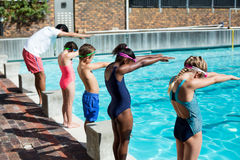 Instructor and little swimmers preparing to jump in pool Royalty Free Stock Photo