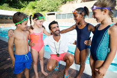 Instructor with little swimmers standing at poolside. Male instructor with little swimmers standing at poolside Royalty Free Stock Photo