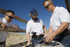 Instructor Loading Gun For Man And Woman Royalty Free Stock Photo