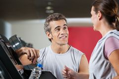 Instructor Looking At Female Client Exercising On Stock Image