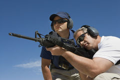 Instructor With Man Aiming Machine Gun Royalty Free Stock Photography
