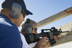 Instructor With Man Aiming Machine Gun stock image