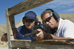 Instructor With Man Aiming Machine Gun Royalty Free Stock Photo