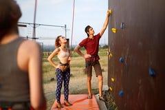 Instructor man guiding pretty slim caucasian woman on rock climbing training wall outdoors. Healthy lifestyle and. Instructor men guiding women on rock climbing Royalty Free Stock Photo