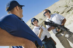 Instructor with man and woman at firing range. Instructor with men and women with weapons at firing range in desert Royalty Free Stock Image