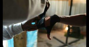 Instructor masculino afroamericano que ayuda al boxeador en abrigo de la mano que lleva en el gimnasio 4k almacen de metraje de vídeo