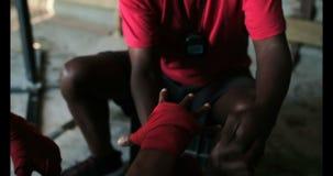 Instructor masculino afroamericano que ayuda al boxeador en abrigo de la mano que lleva en el gimnasio 4k almacen de video