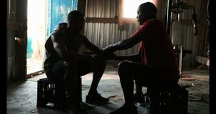 Instructor masculino afroamericano que ayuda al boxeador en abrigo de la mano que lleva en el gimnasio 4k metrajes