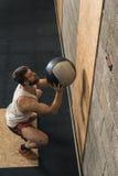 Instructor masculino de Crossfit que hace la bola de la pared Imagenes de archivo