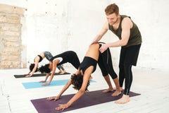 Instructor masculino de la yoga que ayuda a una mujer a hacer estiramientos de la yoga fotografía de archivo