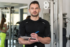 Instructor masculino hermoso With Clipboard In un gimnasio imagenes de archivo
