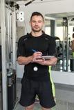 Instructor masculino hermoso With Clipboard In un gimnasio imagen de archivo