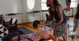 Instructor masculino que ayuda al boxeador de sexo femenino a levantar un barbell 4k almacen de metraje de vídeo