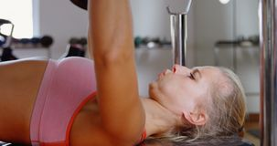 Instructor masculino que ayuda al boxeador de sexo femenino a levantar un barbell 4k metrajes