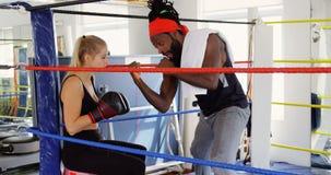 Instructor masculino que da el entrenamiento al boxeador de sexo femenino en el ring de boxeo 4k almacen de video