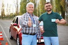 Instructor mayor y hombre feliz con el carné de conducir foto de archivo