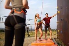 Instructor man guiding pretty slim caucasian woman on rock climbing training wall outdoors. Healthy lifestyle and. Instructor men guiding women on rock climbing Royalty Free Stock Image