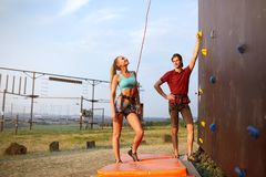 Instructor man guiding pretty slim caucasian woman on rock climbing training wall outdoors. Healthy lifestyle and royalty free stock photography