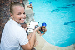 Instructor monitoring time of children swimming in pool. Portrait of female instructor monitoring time of children swimming in pool stock photos