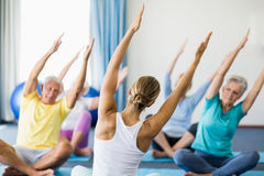 Instructor performing yoga with seniors. During sports class Stock Image