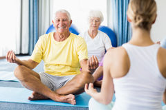 Instructor performing yoga with seniors. During sports class Stock Photo