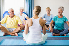 Instructor performing yoga with seniors. During sports class Royalty Free Stock Photo