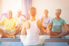 Instructor performing yoga with seniors. During sports class Royalty Free Stock Image