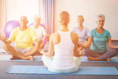 Instructor performing yoga with seniors. During sports class Royalty Free Stock Photos