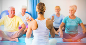 Instructor performing yoga with seniors. During sports class Royalty Free Stock Photography
