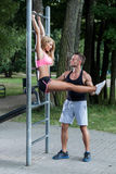 Instructor personal asegurando a la mujer durante ejercicio Fotos de archivo libres de regalías