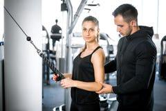 Instructor personal de la aptitud con su cliente en gimnasio imagen de archivo