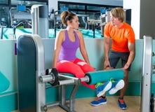 Instructor personal de la mujer del entrenamiento de la extensión de la pierna del gimnasio Fotos de archivo