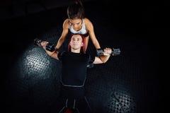 Instructor personal de sexo femenino de la aptitud que ayuda a un hombre joven en el gimnasio Imagen de archivo libre de regalías