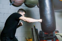 Instructor personal del boxeo trenes del individuo con la pera del boxeo Fotografía de archivo