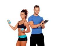 Instructor personal hermoso con la muchacha hermosa con pesas de gimnasia Fotos de archivo libres de regalías