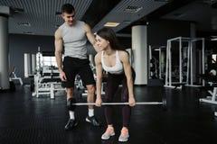 Instructor personal posiciones en cuclillas de ayuda de una mujer joven con los dumbells en un gimnasio fotografía de archivo