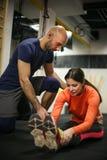 Instructor personal que entrena a su cliente en el gimnasio imagen de archivo libre de regalías