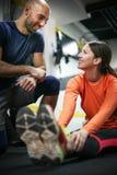 Instructor personal que entrena a su cliente en el gimnasio fotografía de archivo