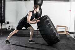 Instructor personal que mueve de un tirón un neumático en un gimnasio mientras que da instrucciones un modelo femenino de la apti imágenes de archivo libres de regalías