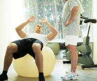 Instructor personal y hombre mayor en club de fitness imágenes de archivo libres de regalías