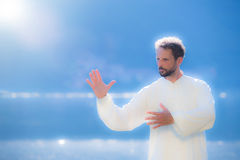 An instructor practice of Tai Chi Chuan. An instructor in white dress practice of Tai Chi Chuan Stock Images