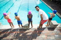 Instructor preparing little swimmers to jump into swimming pool. Male instructor preparing little swimmers to jump into swimming pool Royalty Free Stock Photo