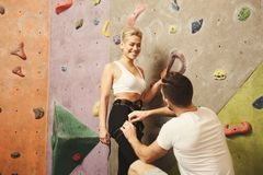 Instructor preparing young woman for climbing stock photos